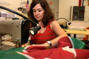 Flags Unlimited Inc. Rosie Molina, seamstress, sewing a customers flag order.