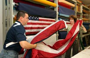 Flags Unlimited Inc. Kevin Lynch, marketing coordinator, and Laura Squires, office manager, fold a 12-foot by 18-foot flag just finished for a local car dealer.