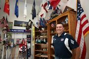 Flags Unlimited Inc. Kevin Lynch, marketing coordinator, in the flag showroom with military, vintage style, novelty and state flags.