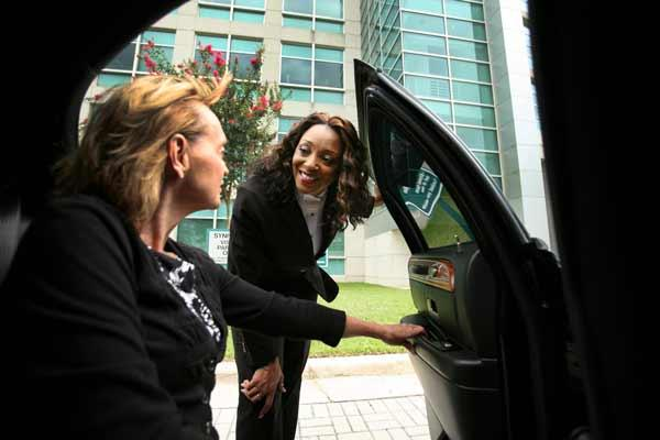 Beleria Floyd, CEO of Grand Dames Car Service Inc., right, helps client Leigh Hennen, chief human resources officer of Syniverse in Tampa, get settled in for a trip to Tampa International Airport.