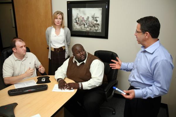 Jim Johnson, learning technology services manager for Intelladon, Kristan Evans, marketing director, and Gregory Carroll, customer support specialist, meet with CEO Marc Blumenthal.