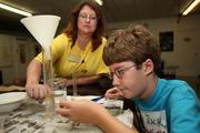 The Science Center of Pinellas, Inc. dba Grant Hatch, 11, conducts an oil spill experiment in a local ecosystems class with instructor Marleen Jones.