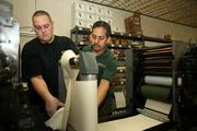 Our Town America. Joel Prokosch, press man, and Jose Milian, inserter operator, working on the press before a run.