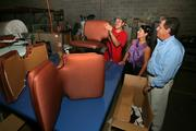 Bill Adams, president, and Joni Adams, CEO, with Persio Castro, upholsterer, refurbishing cafe chairs.