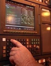 Terry Pomeroy, CNC machinist, edits a computer program.
