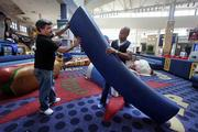 The San Francisco Upholstery Group's Ricardo Cruz, trimmer, and Founder Lamar Dula reupholster a booth in the kids play area of Westfield Citrus Park Mall.