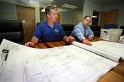 Marshall and Rhett Stevens review blueprints showing how they expanded their business.