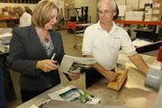 Karen O'Brien, co-owner and president of ThinkShapes Mail, discusses finishing on a job with David Parz, bindery manager in the bindery and shipping department.