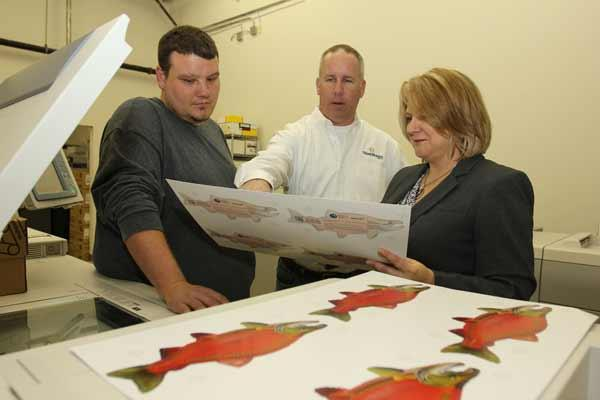Derek Yates, production manager for ThinkShapes Mail, Jim O'Brien, co-owner and vice president of sales and marketing, and Karen O'Brien, co-owner and president, discuss a proof for a fish-shaped mailer.