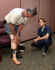 Patient George May gets his prosthetic adjusted with the help of David Robinson, anaplastologist.