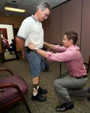 Patient George May gets his prosthetic adjusted and measured for proper height by Greg Bauer, president of Westcoast Brace & Limb.