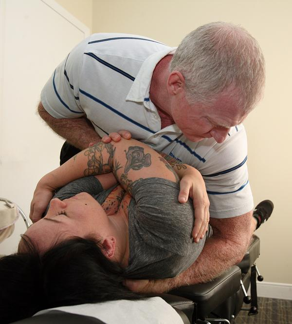Chiropractor Erce Phillips, owner of Ybor City Chiropractic and Hudson Chiropractic and Rehab, treats patient, Brandy Moore, member of Tampa Bay Derby Darlins, in the Ybor office.