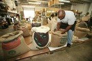 Fernois Bradberry, coffee roaster, checks bags of coffee beans before roasting.