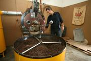 Co-owner Raphael Perrier with coffee beans being roasted.