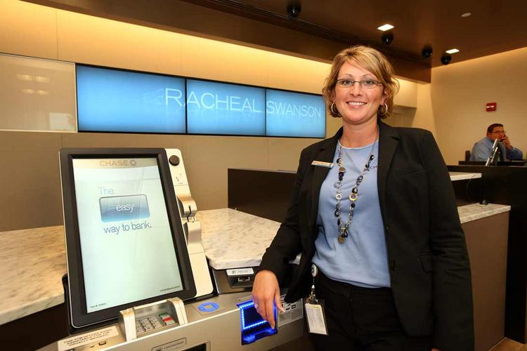 Racheal Swanson, branch manager at the Chase Bank at One Sarasota Tower, with a new self-service banking kiosk. The new branch also includes plasma TVs and private client rooms.