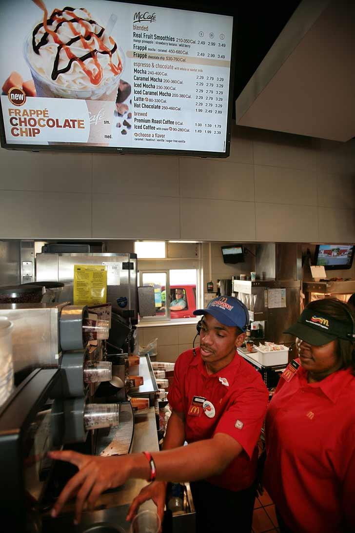 McDonald's crew members Frank Ellison and Audrey Williams work beneath the new menu display board with calorie counts.