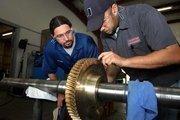 David Fay inspects a gear with technician Loren Hepler.
