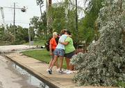 The owners of tornado-destroyed homes in Pass-A-Grille hug across the street with major tree uprooting and damage.