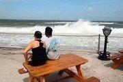 People watch the crashing surf.