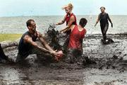 """Team """"Bang It"""" tries to prevent their competitors from scoring a touchdown during the Extreme Mud Wars in downtown St. Petersburg."""