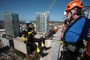 Joanie Cupler gets instruction from Wm Shrewsbury with AWS Carpenter Contractors, a volunteer with Over The Edge USA, before rappelling from the 22-story Franklin Exchange building in downtown Tampa.