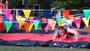 """A runner scrambles through the """"Jelly Belly Crawl,"""" one of four obstacles in the 7 Campus Scramble, part of the Greensboro Collegiate Biscuitville Bowl."""
