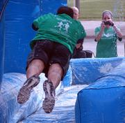 A runner flies head-first into the Buttermilk Slip-n-Slide as part of the 7 Campus Scramble on April 21 at Center City Park in downtown Greensboro.