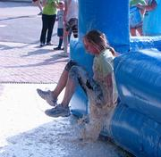 """Competitors emerged covered after a slide down the """"buttermilk"""" obstacle at the 7 Campus Scramble."""