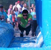 """A team member dives head-first into the Buttermilk Slip-n-Slide, filled with """"buttermilk,"""" which was actually a mixture of water and flour."""