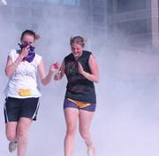 """Two runners make their way through the """"Flour Shower,"""" a thick cloud of flour blown by large fans that seemed to create a fog around the entire course."""