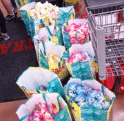 Hawaiian-shirted store crew members doled out leis to shoppers. By 8:20 a.m., there were just a few bags left; by 8:30 a.m., the leis were all handed out.
