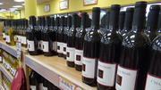 """By 8:30 a.m., wine lovers had already made a dent in the famed """"Two Buck Chuck"""" wines. There are four white wines and three red wines available for $2.99 per bottle."""