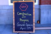 A  sign indicates that construction is underway for the April 12th grand opening of the new Whole Foods store in Greensboro.