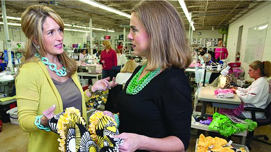 Brandi Temple, left, CEO and founder of Lolly Wolly Doodle, talks with Amy Vestal, vice president of sales and design in the company's sewing area. Lolly Wolly Doodle does much of its business on Facebook. Click here to see more photos.