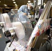 Terance Little monitors a Secret antiperspirant production line at Proctor & Gamble's Browns Summit plant.