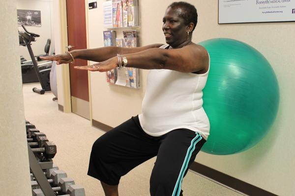 Allegacy Federal Credit Union equity processor Jackie Wilkins using a fitness ball while working out  at Allegacy's on-site gym. Wilkins credits Allegacy's wellness program  with helping her to lose weight and control her diabetes.