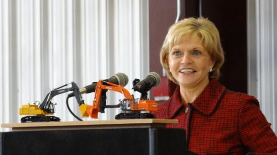 Gov. Beverly Perdue stands behind two models of excavators produced at Deere-Hitachi Construction Machinery Corp. on Friday while announcing the company will invest $97 million and hire 340 workers to expand production capacity.