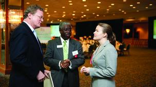 Jillian Gibson and Ward Miller of NewBridge Bank talk with Douglas W. Copeland, at left, publisher of The Business Journal.