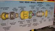 An instructional display for the assembly of a rear wheel for a Caterpillar mining truck, which can be seen in the background. The wheels and axles will be produced at Caterpillar's new Winston-Salem plant.