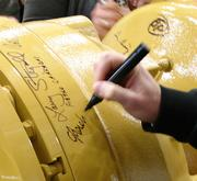 Attendees at the grand opening for Caterpillar's Winston-Salem plant were asked to sign their names to an axle that will be used to commemorate the event.