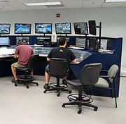 FedEx's proprietary Integrated Sortation System allows central control workers to monitor the package sorting process. If one chute is full, the load-side manager can go into the ISS system and add another to the busy destination. Another worker communicates to a switcher on the ground outside to determine which load side that trailers should go to when they arrive. That worker can also pull up a trailer's real-time location on a map.