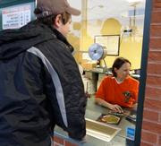 A Greensboro Grasshoppers fan buys a ticket for the team's season opener Thursday night. The game was canceled because of rain.