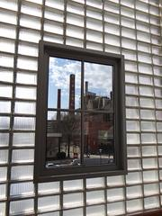 A view from a window on the south side of Wake Forest Biotech Place of a smokestack in the neighboring R.J. Reynolds manufacturing plant. Two adjoining RJR buildings, built in 1937 and 1962, were renovated to create the 242,000-square-foot Wake Forest Biotech Place. The south end of the building includes more than 65,000 glass blocks like those seen here.