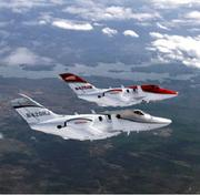 """Honda Aircraft Co. has completed one year of flight test with its FAA-conforming aircraft, """"F1,"""" the silver aircraft in foreground, and its first month of flight test with """"F2,"""" the red aircraft in background."""