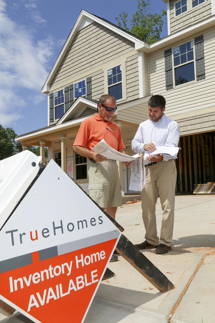 Jeff Cook, left, personal builder with True Homes, and Brian McWhirter, True Homes' managing partner, go over plans at the site of a development at Reedy Fork.