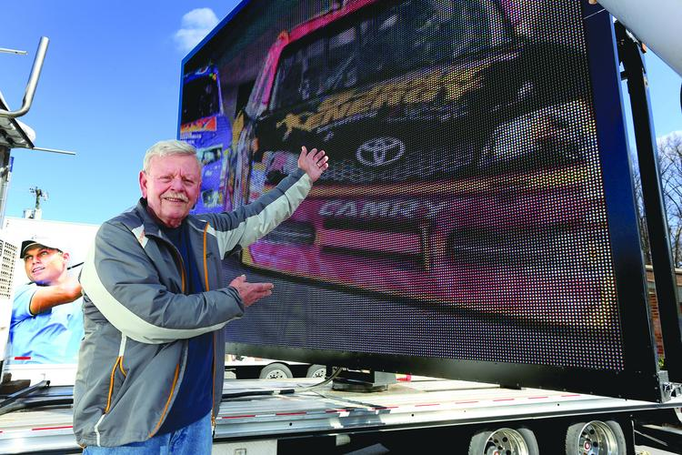J.D. Bruhn, president of Special Event Production Inc. in Clemmons, stands with one of his company's large digital screens used at outdoor events.