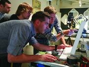 Randy Wells, right, vice president of Stanley marketing and brand development, points at digital images on a computer as the creative team looks on.