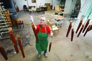 Margaret McDaniels hangs furniture pieces to dry after being sprayed.