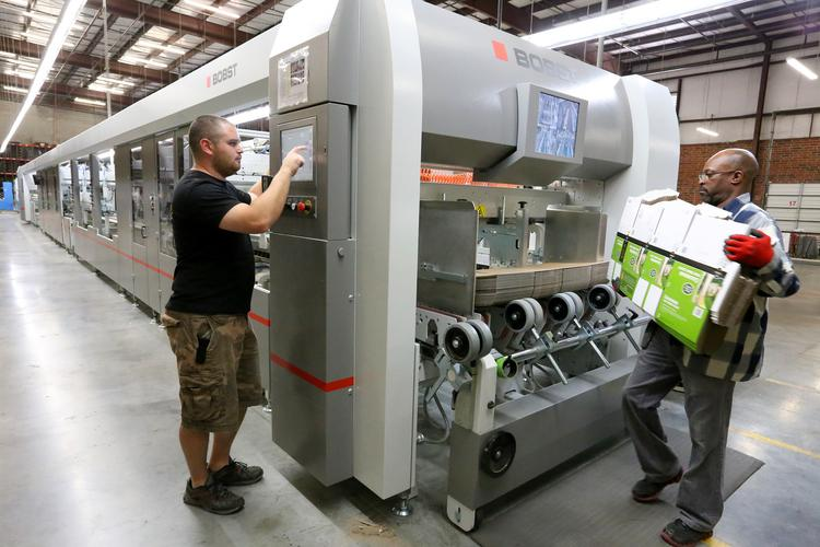Jordan Pressley, left, operates the highly-automated Masterfold 170 at Packrite in High Point. Darryl Ledbetter feeds materials into the machine.