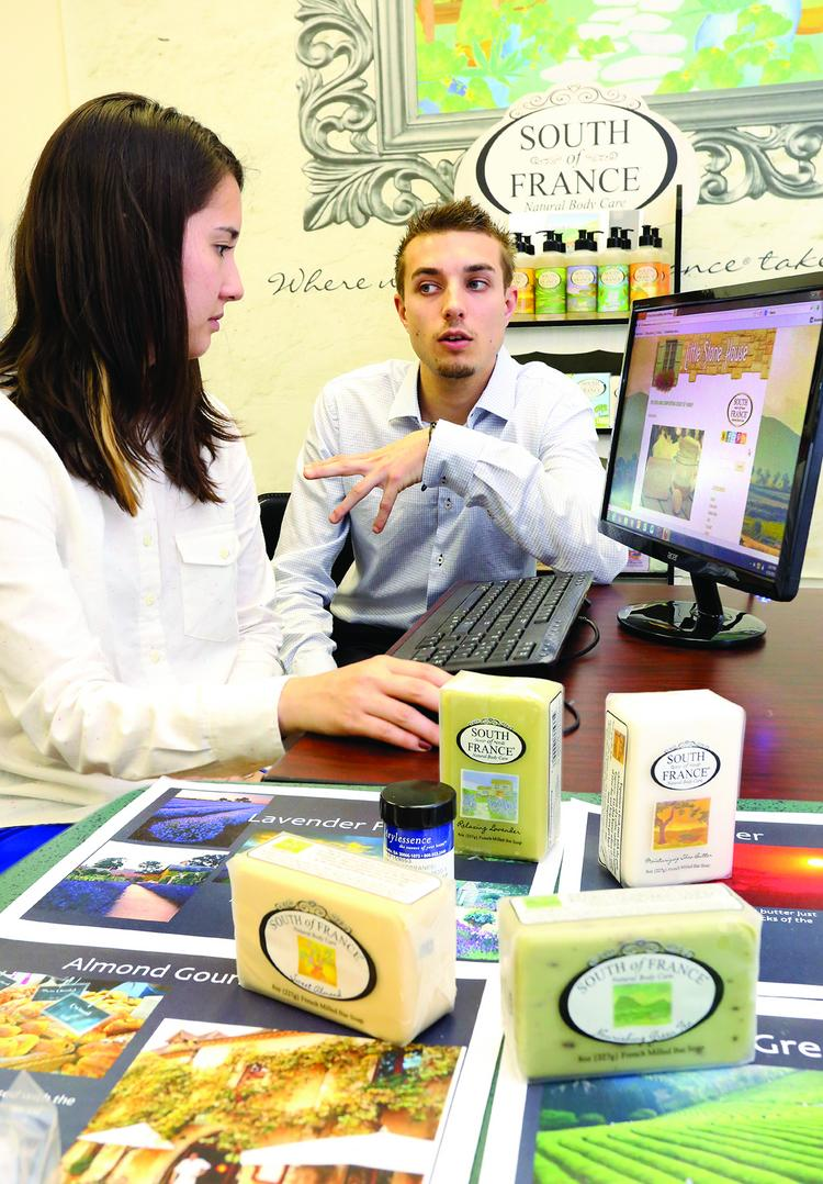 Chris Valenta, left, an account executive with The King's English in Greensboro, meets with client Clement Hanocque, marketing assistant with South of France Natural Body Care, about its responsive website.